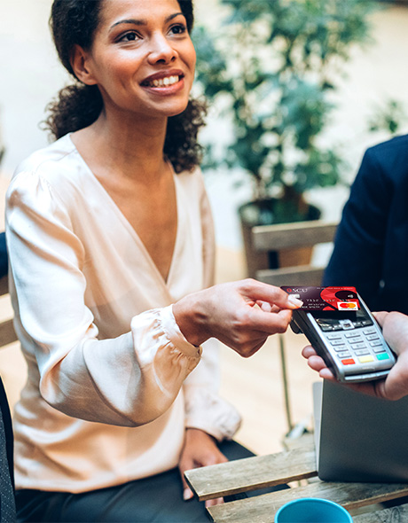 Woman holds an SCU Collabria® business credit card to a payment terminal