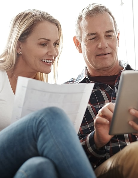 Couple in their 50 – 60s reviews their retirement plan on their tablet