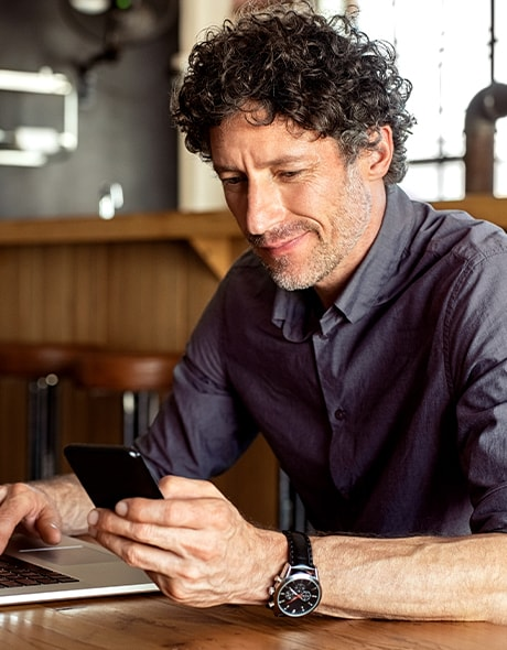 Business owner looks at his business accounts on his phone