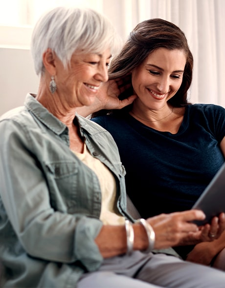 Mother and daughter look at a tablet and discuss estate planning