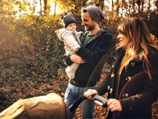 Young couple walks through the woods with their two young children