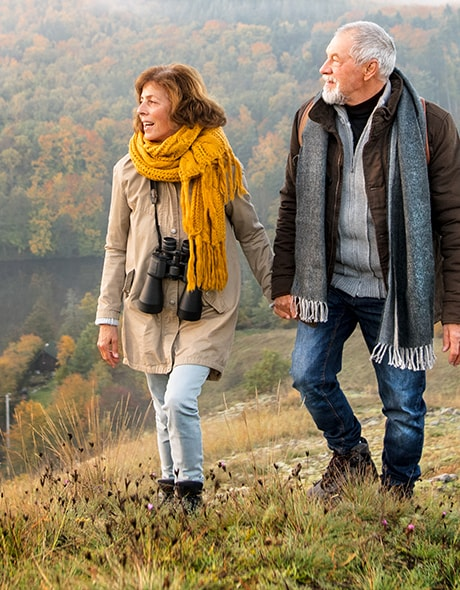 Older couple hikes up a hill in the fall