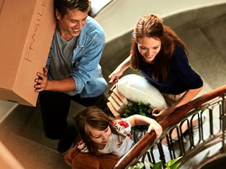 A young family carries boxes into their new home