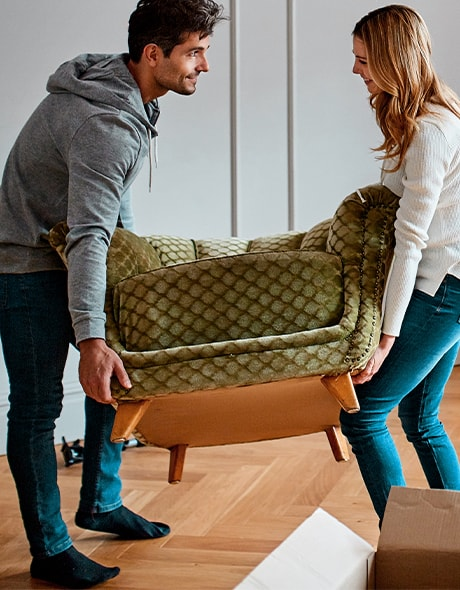 Young couple moving a couch into their new home