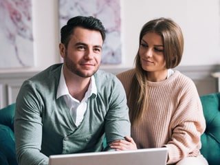 Young couple sits with a a laptop and plans their savings goals