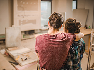 Young couple looks at the progress they've made on their home renovation