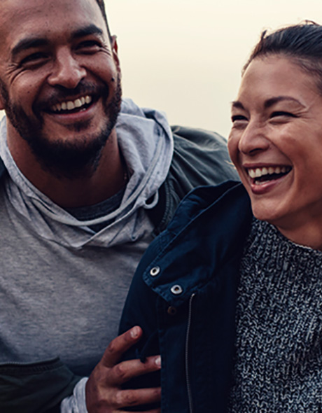 Man and woman smiling together outside
