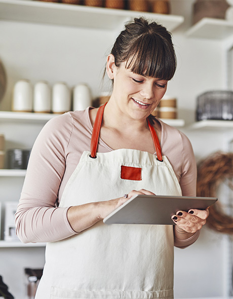 Bakery owner reviews her financial statement on her tablet