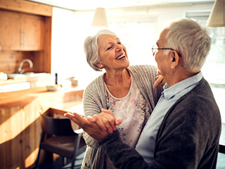 Retired couple smiling and dancing in their kitchen