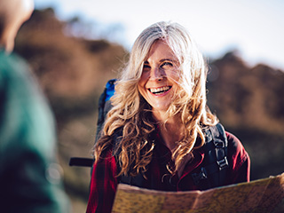 Older woman smiles at her hiking partner as she holds a map